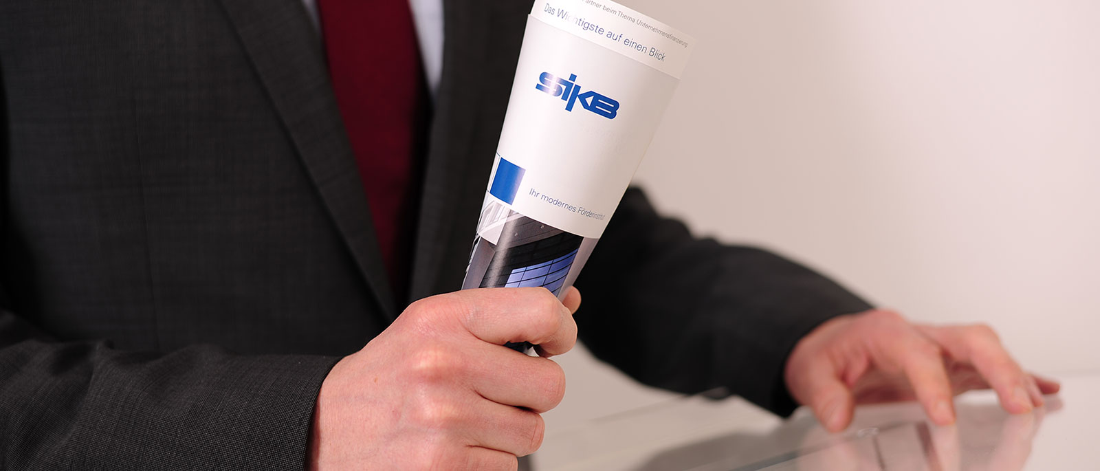 Person hält Flyer von SIKB in Hand